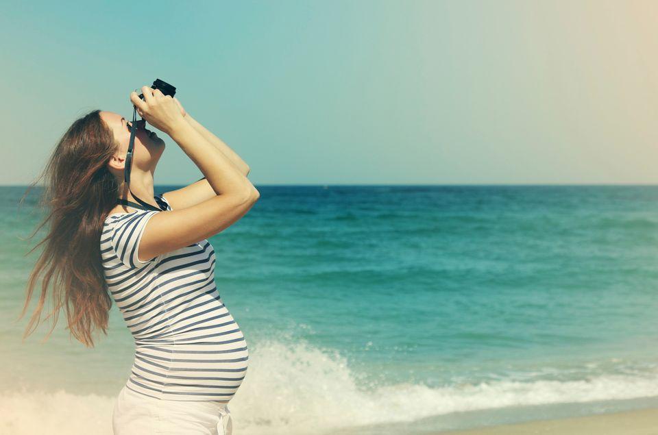 Woman by the sea looking up through binoculars