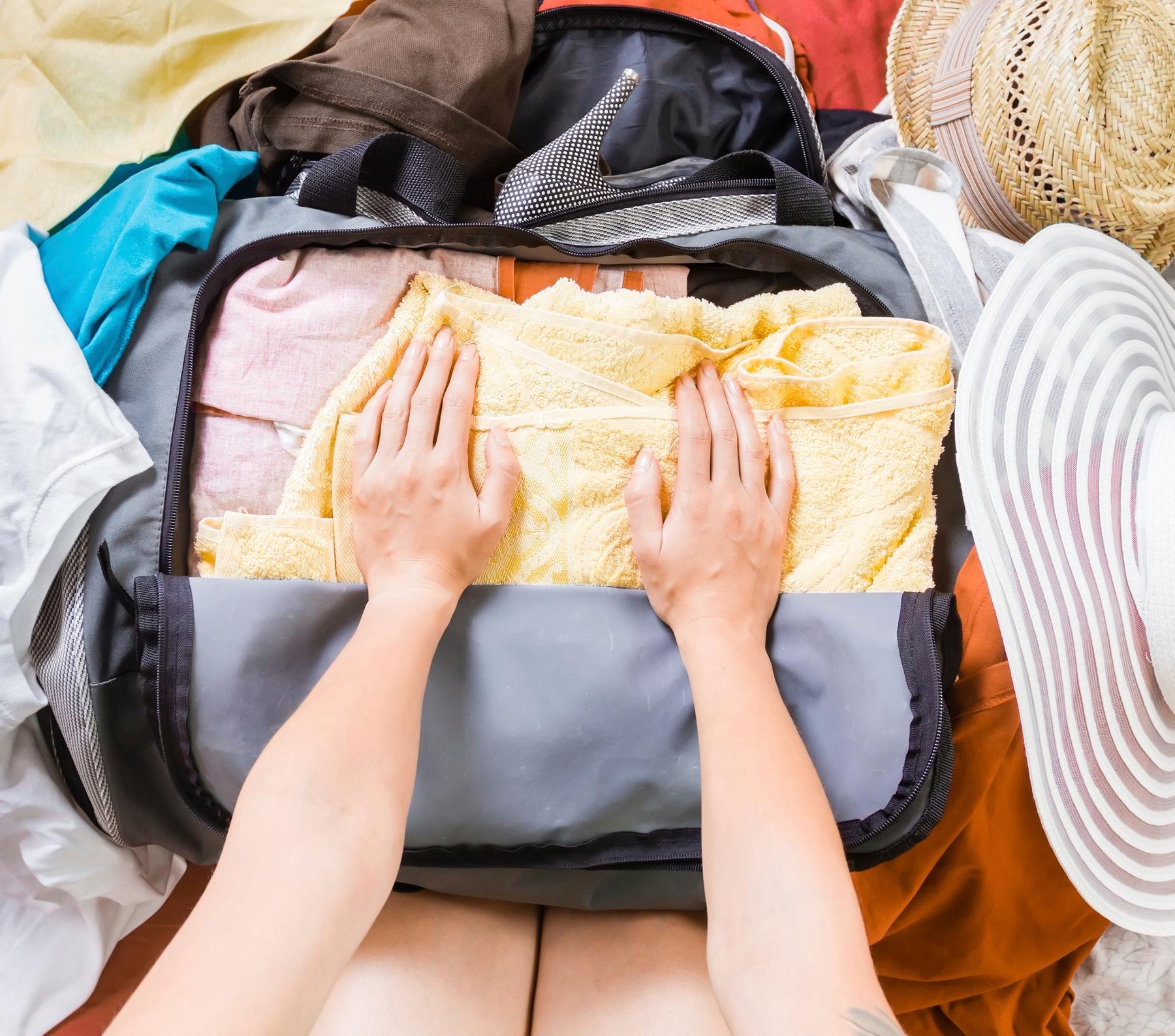 Pessoa montando sua bagagem de mão para a viagem.