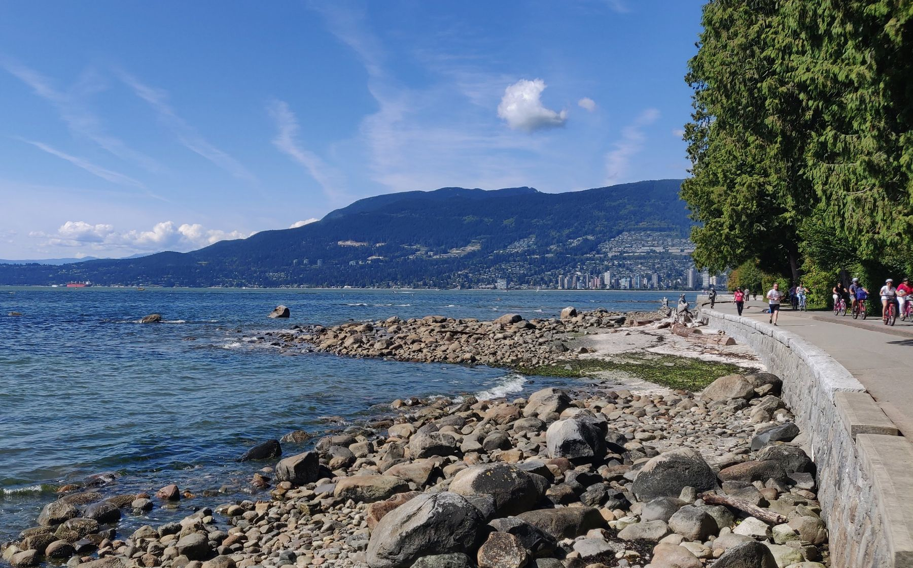 rocks by the shore and people bicycling on the seawall in Vancouver by Stanley Park. Rocky Mountains in the background.
