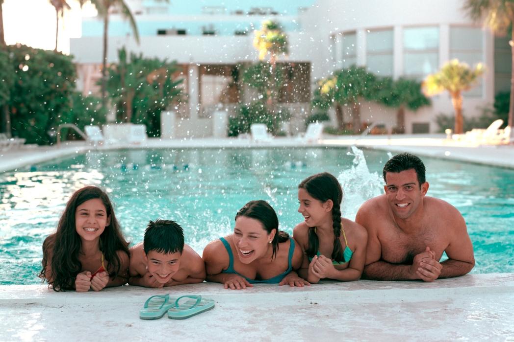 Γονείς και παιδιά απολαμβάνουν βουτιές στην πισίνα ξενοδοχείου