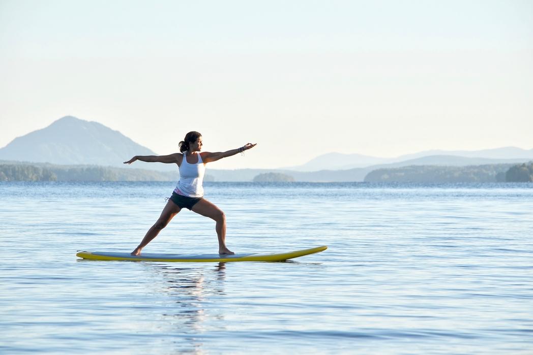 Γυναίκα κάνει γιόγκα σε σανίδα στη θάλασσα