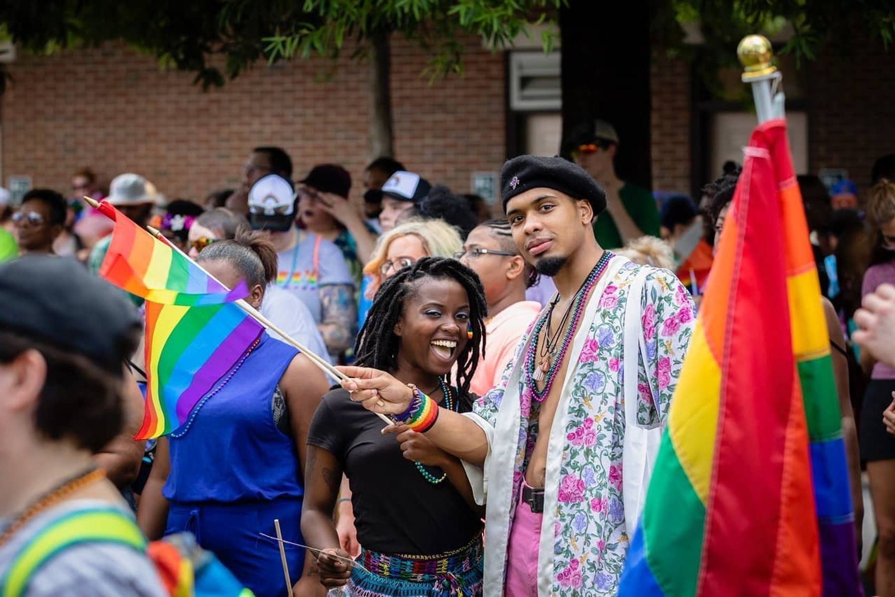 Two people celebrating Pride in Augusta, holding rainbow Pride flags.
