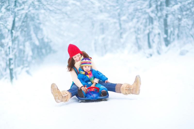Ребенок и его мама спускаются с ледовой горки на санках.