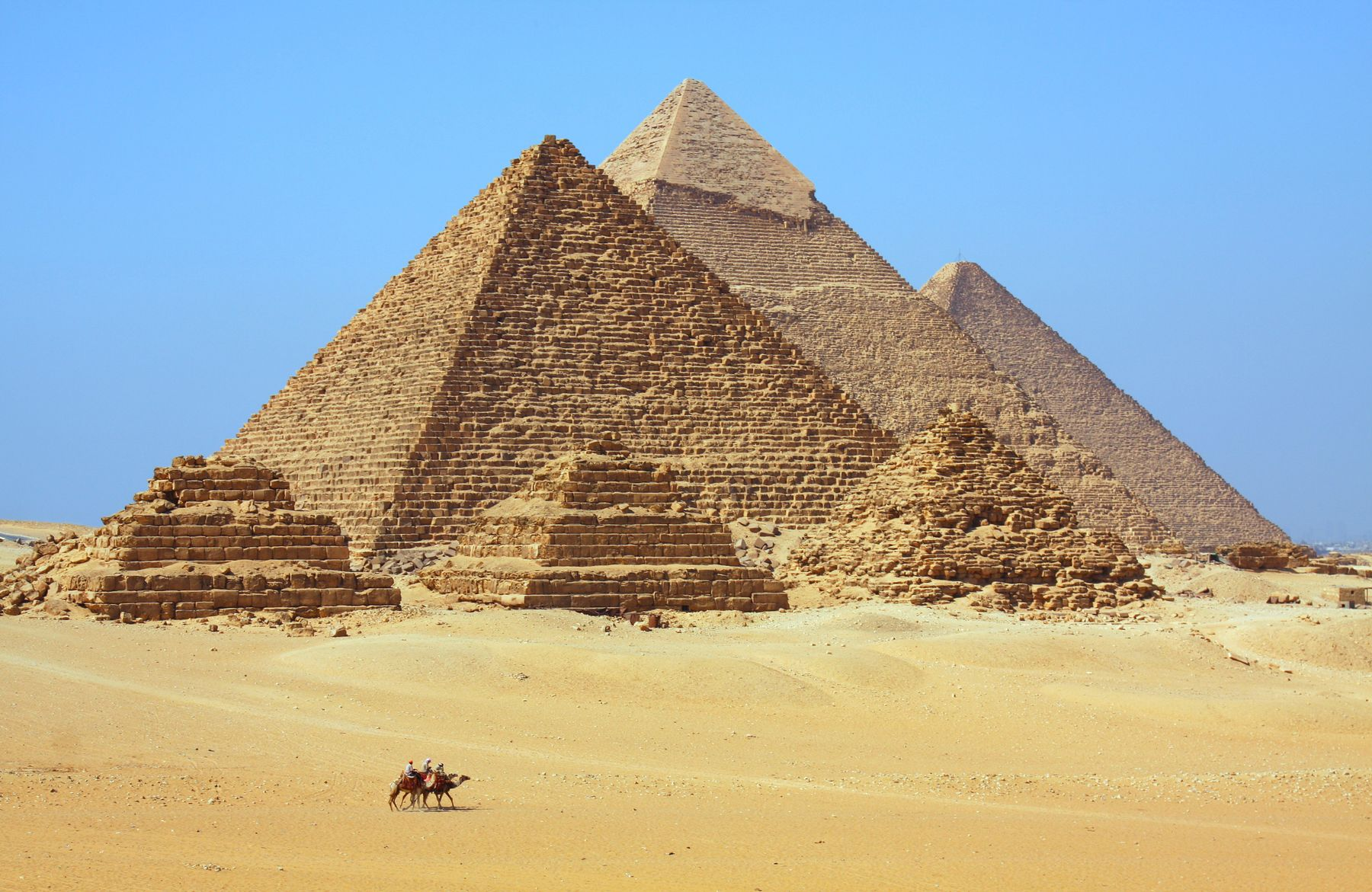 Vue de trois petites pyramides et trois grandes pyramides derrière eux