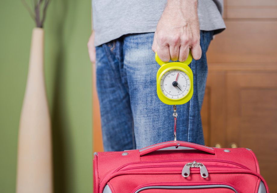 Man weighing a pink suitcase with a luggage scale