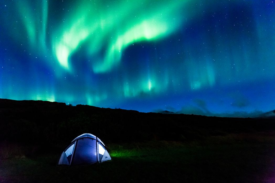 Camping in nature to catch the Northern Lights in action