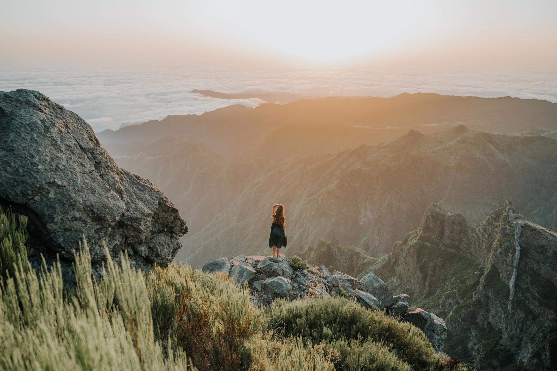 Frau bestaunt die Aussicht auf einer Wanderung während ihrer Soloreise.