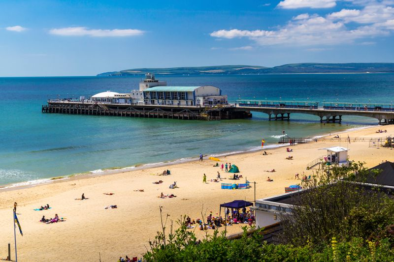 Beach in the UK, a pier and sunbathers