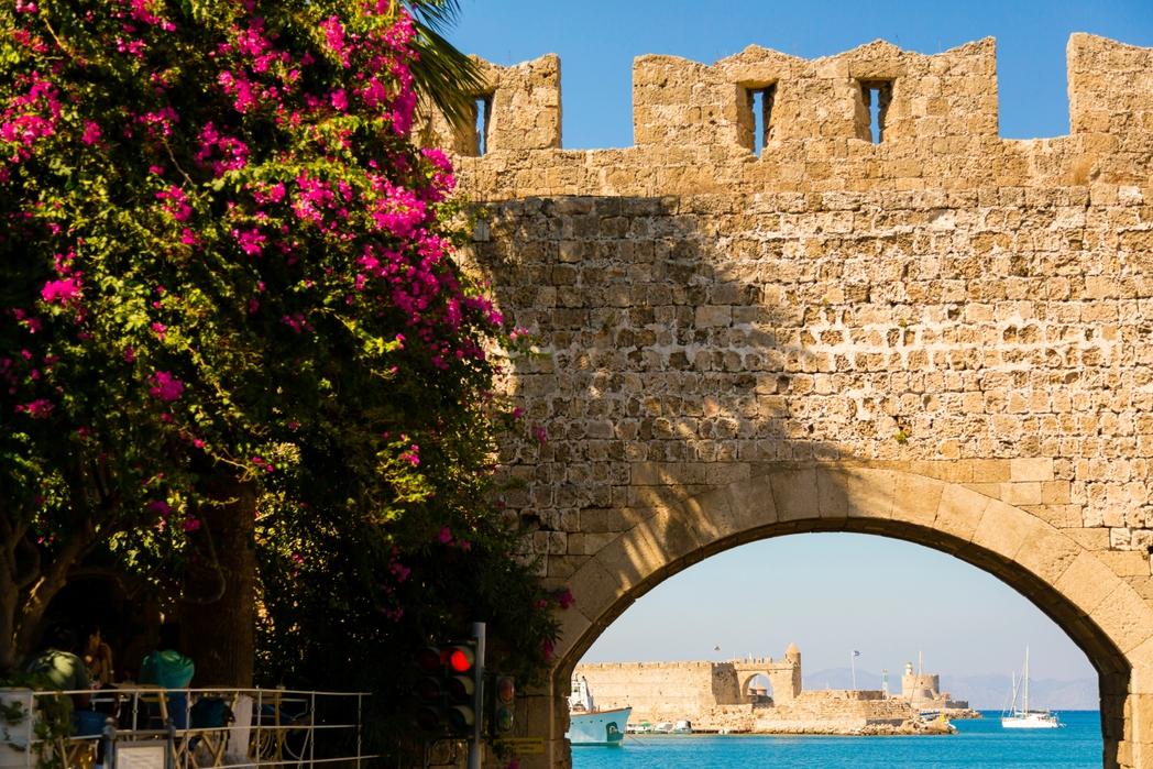 Bουκαμβίλια δίνει χρώμα στη μεσαιωνική Πόλη της Ρόδου, στο βάθος θάλασσα