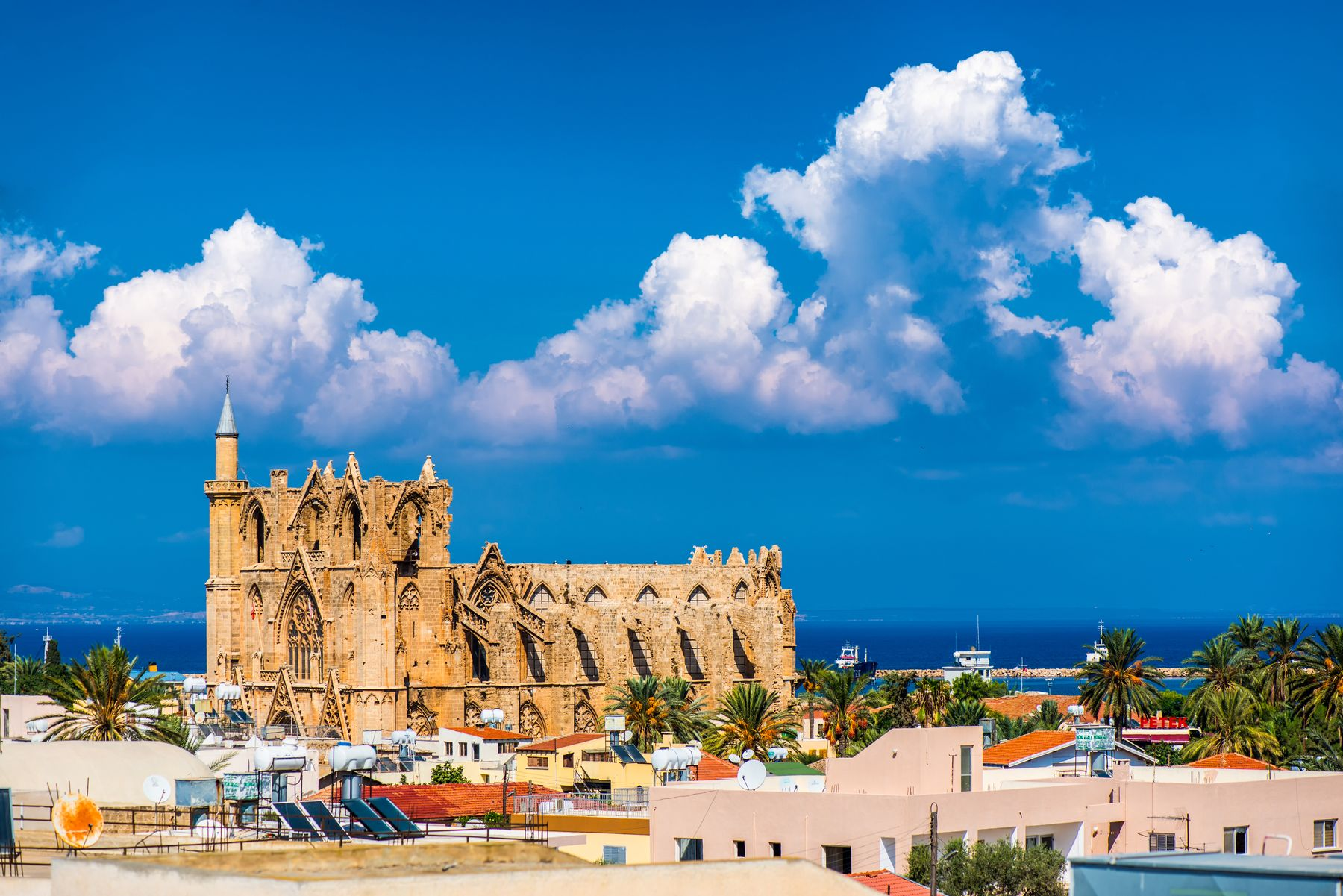 Town in Cyprus with a cathedral, palm trees, and beach in the background. Cyprus is consistently a popular and warm place for Canadians to travel to in December.