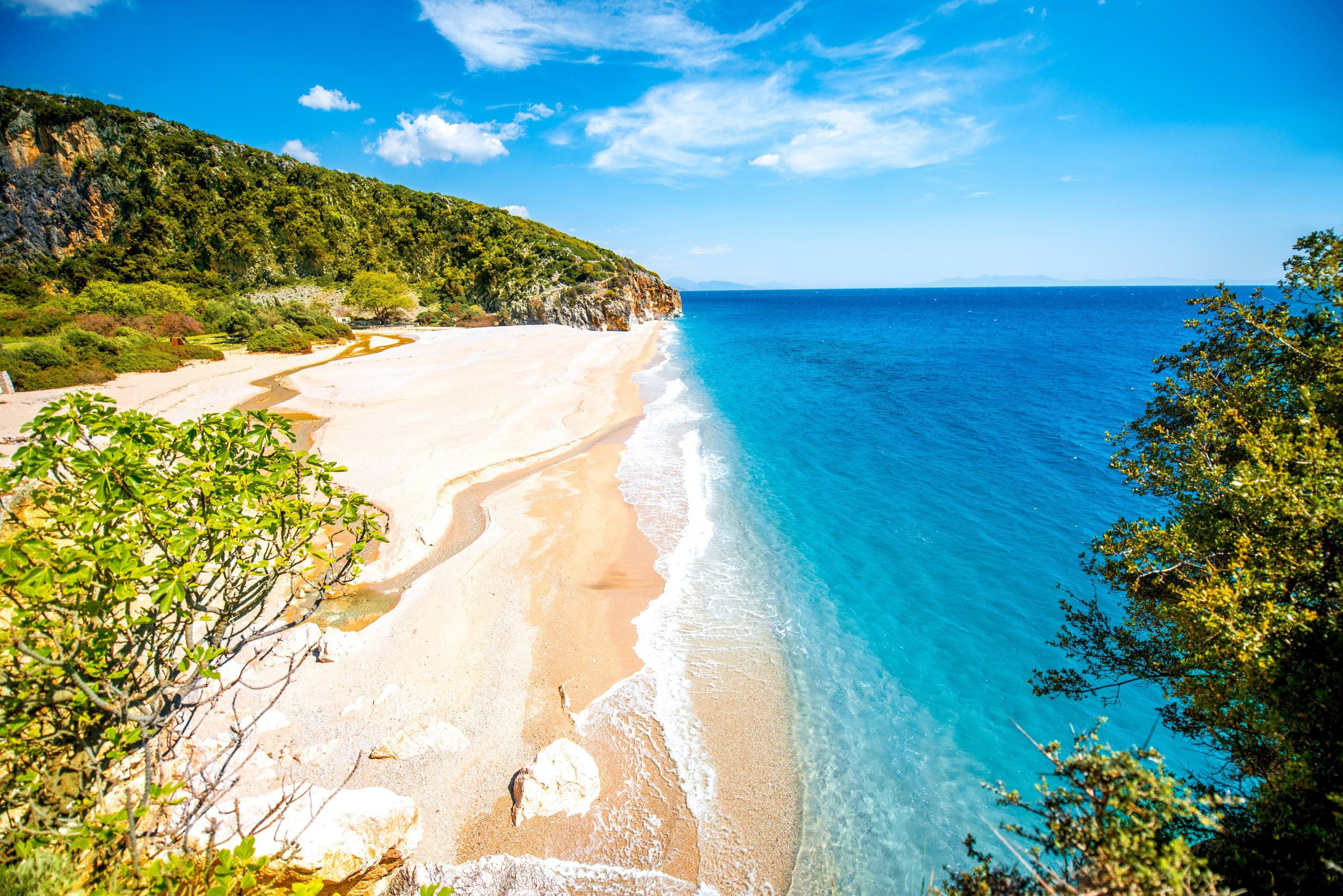 Beach flanked by verdant hills in Albania - one of the best destinations in the Med for summer 2019