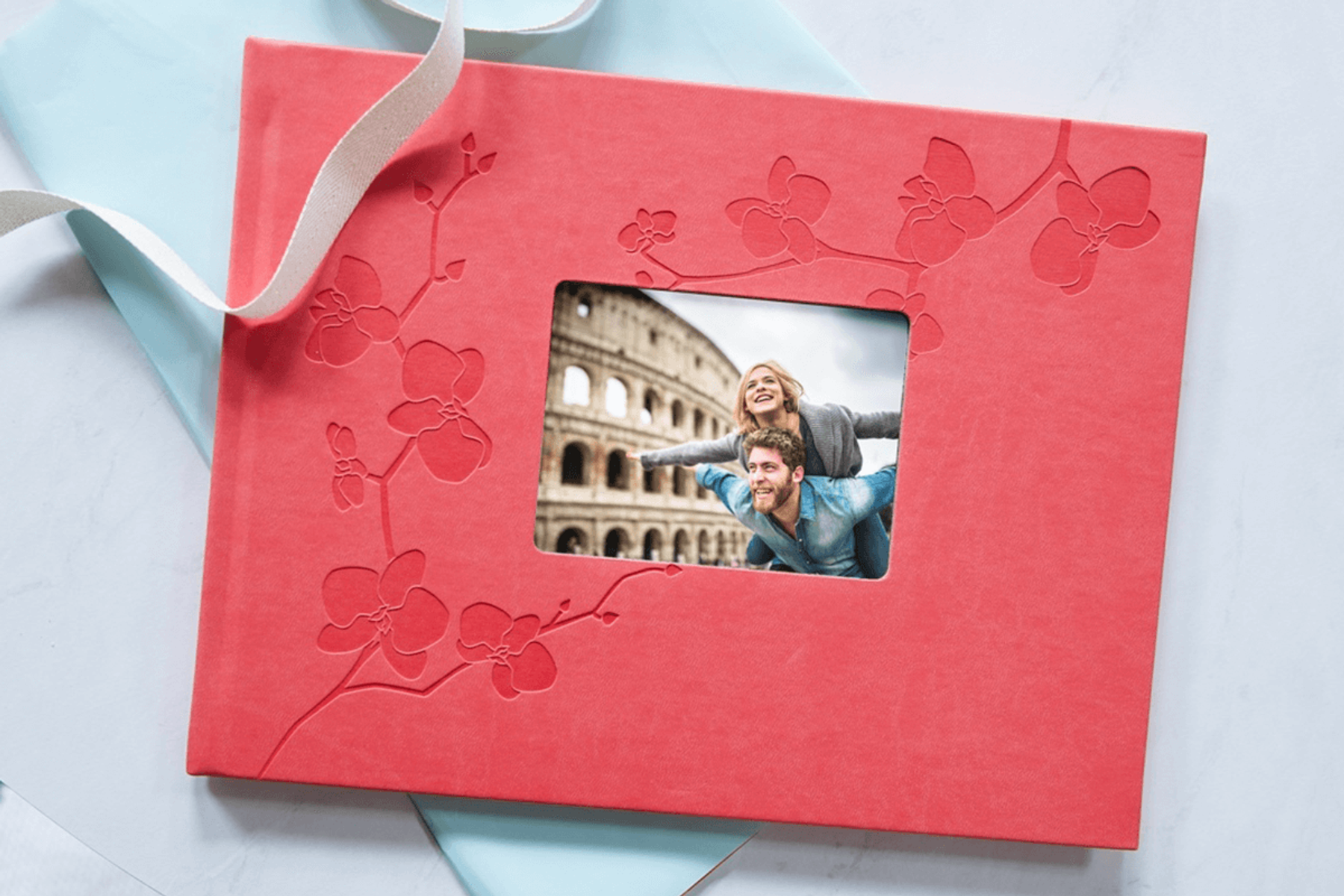 Photo book front cover with window showing couple exploring the colosseum.
