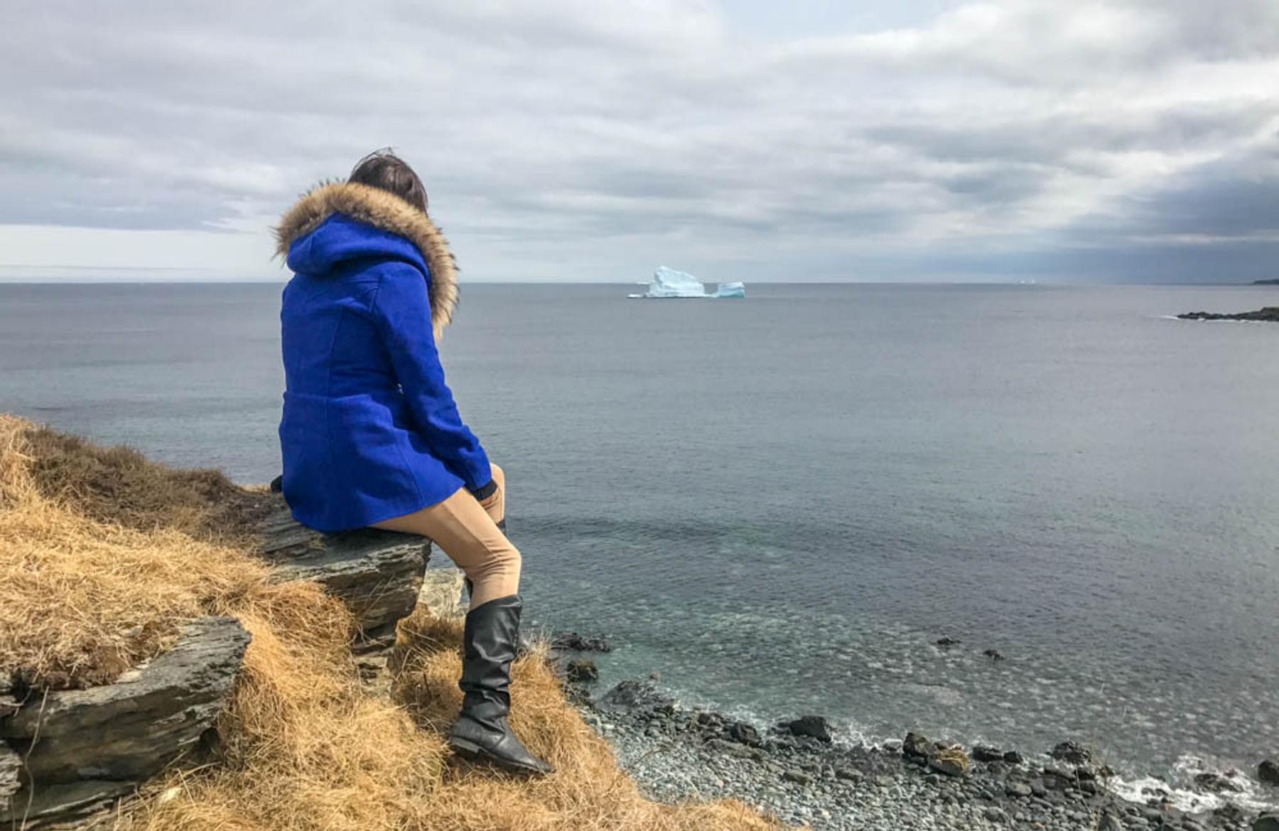Blogger Lora sitting on a rock by the coastline of Newfoundland in Iceberg Alley, a dream destination in Canada