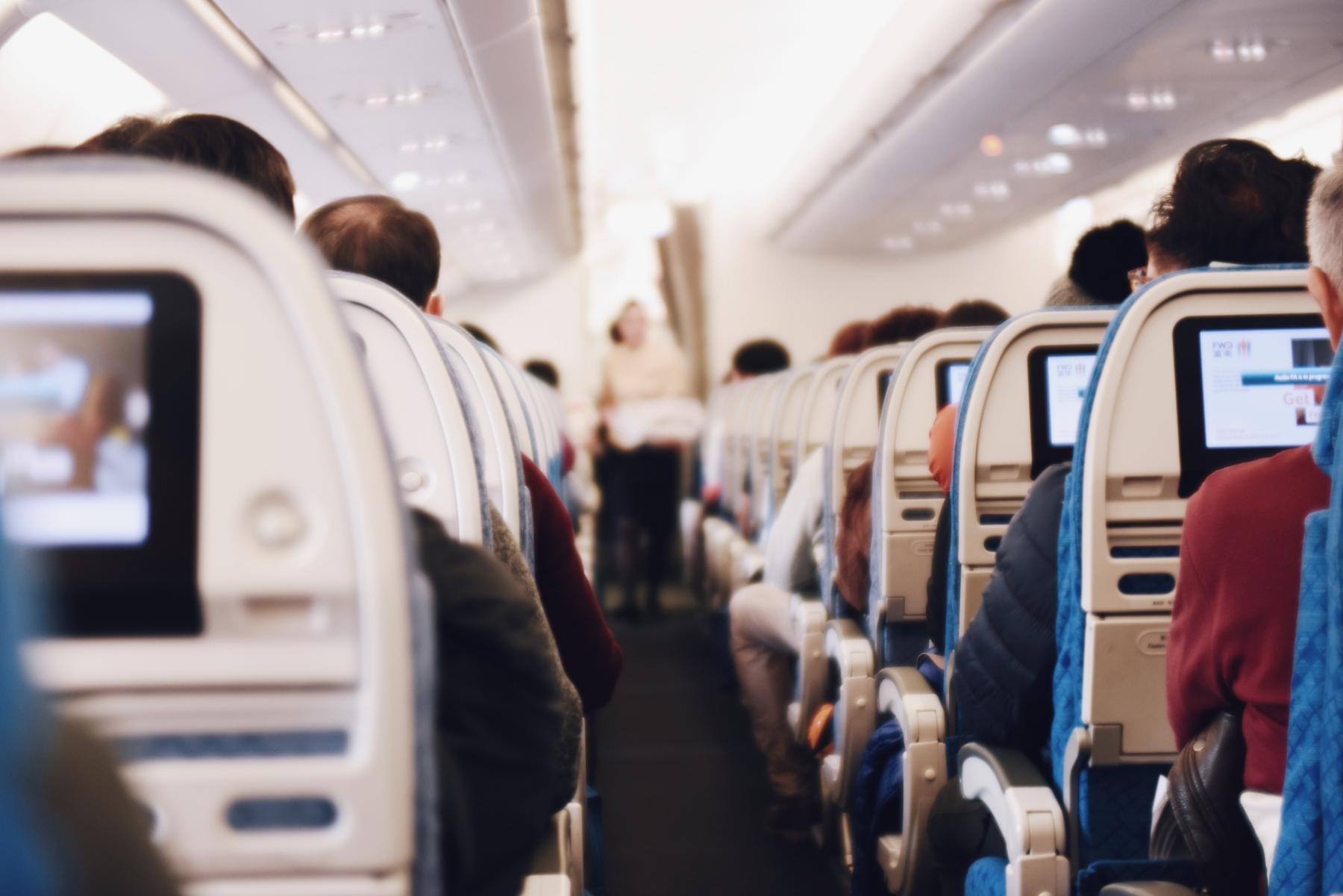 An air steward hands out snacks in an airplane cabin.