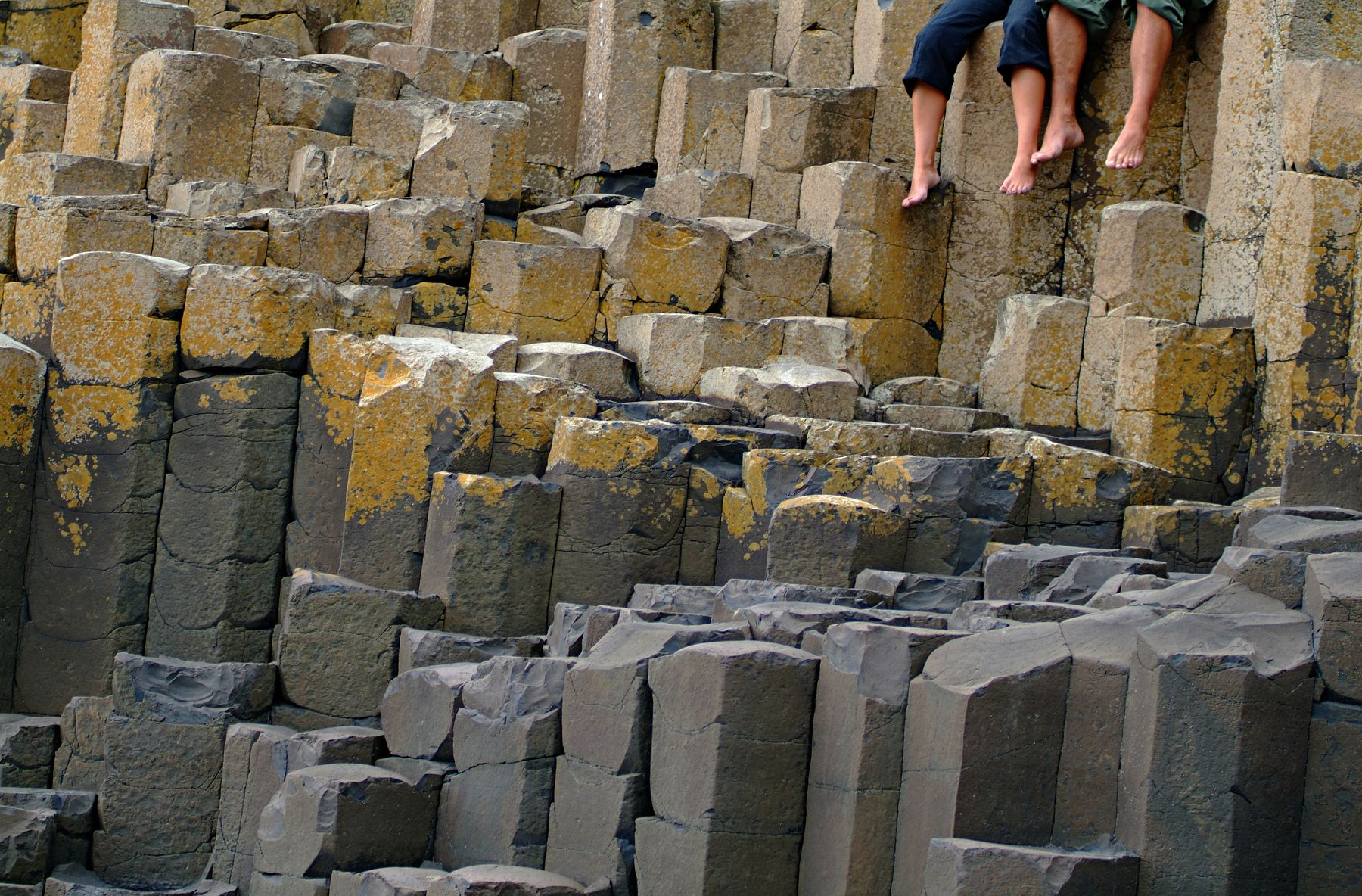 Couple sitting on the Giant's Causeway, Causeway Coast, Northern Ireland