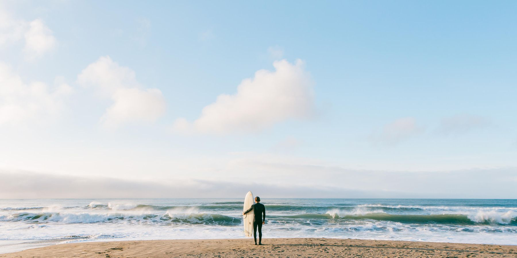 Person with a surfboard looking at the sea