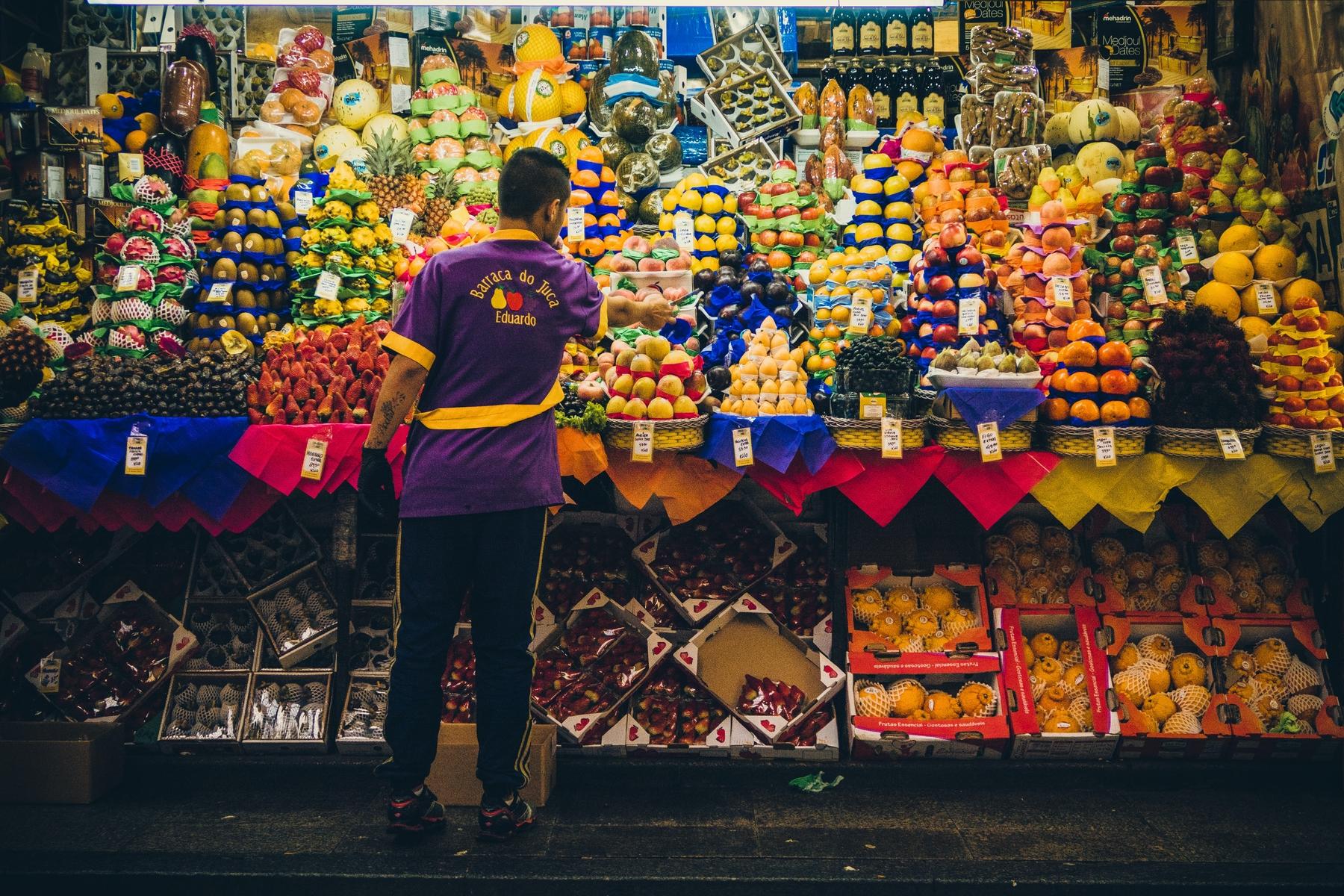 Vendedor em frente aa uma banca de frutas no Mercado Municipal de São Paulo.