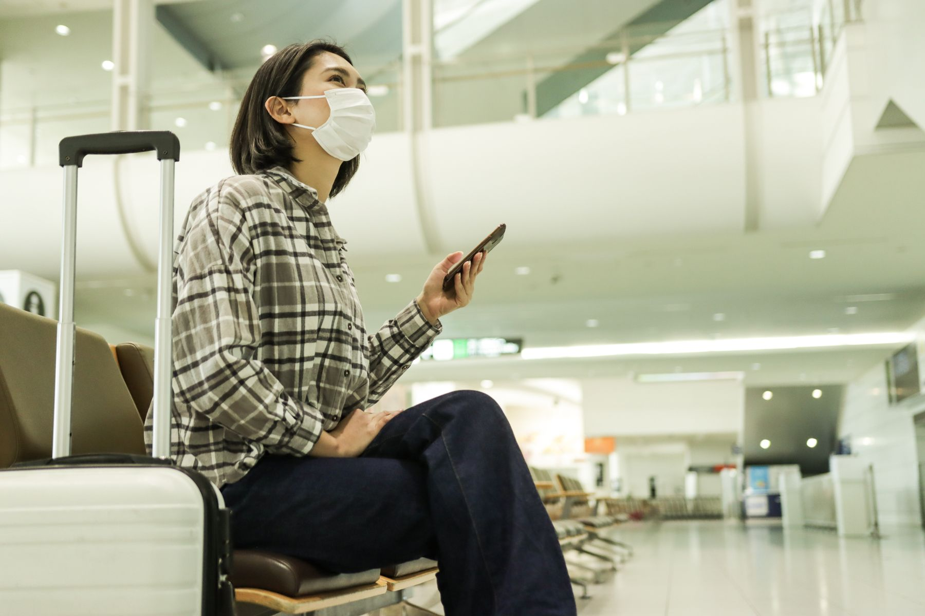 Woman wearing a mask sitting inside of an airport