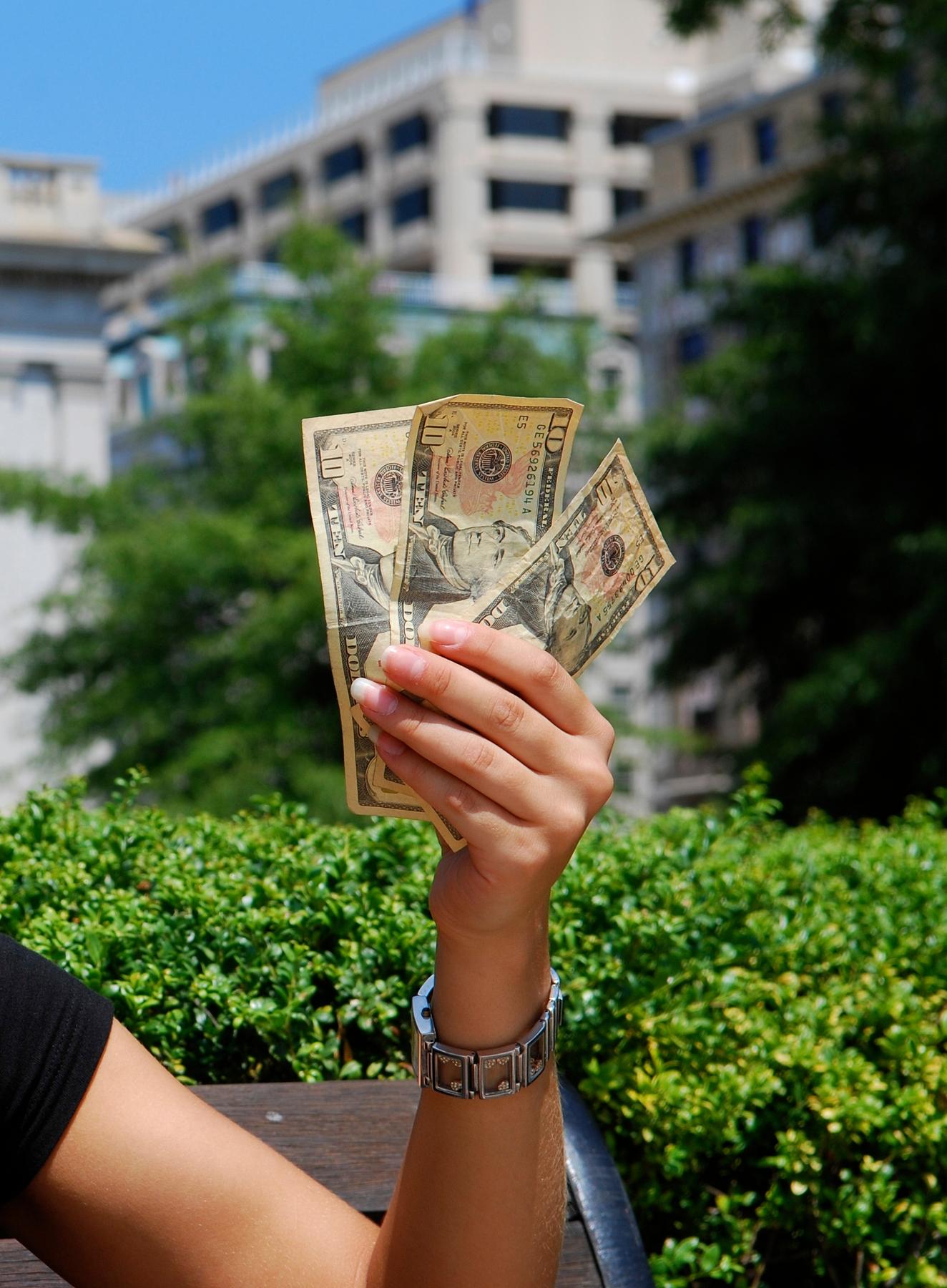 a female hand holds three ten-dollar bills as a potential flight refund