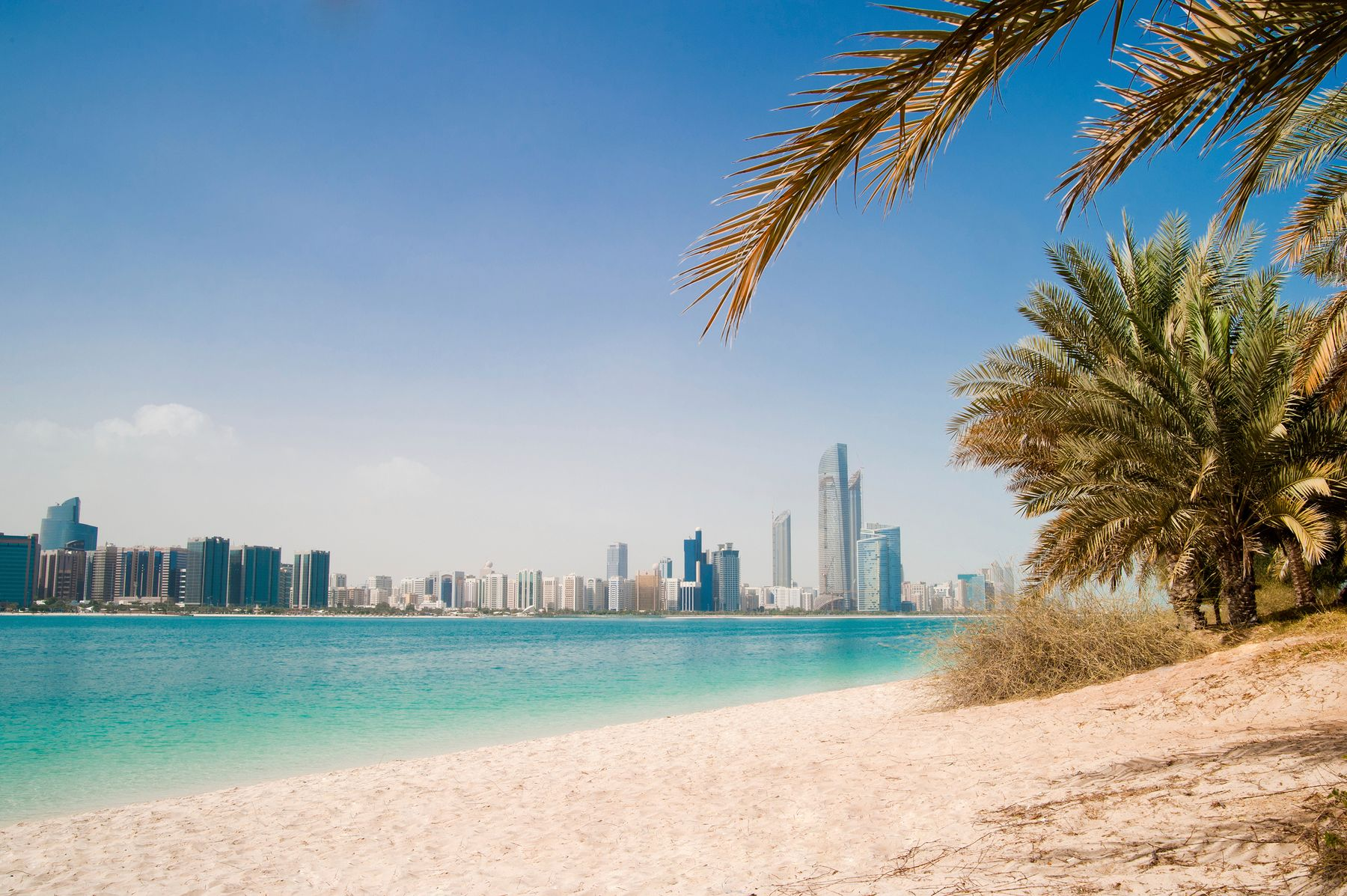 The skyline of dream destination Dubai sits in the background, while turquoise water and a white palm-fringed beach are in the foreground