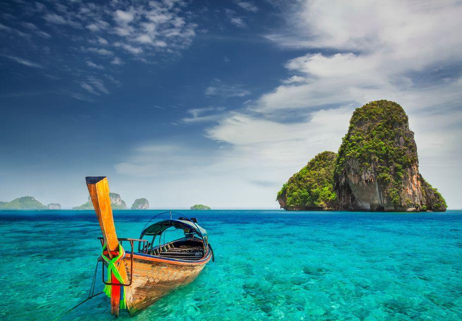 Πλώρη παραδοσιακής βάρκας ταξιδεύει σε τιρκουάζ νέρα, ανάμεσα στα καρστ του Πουκέτ