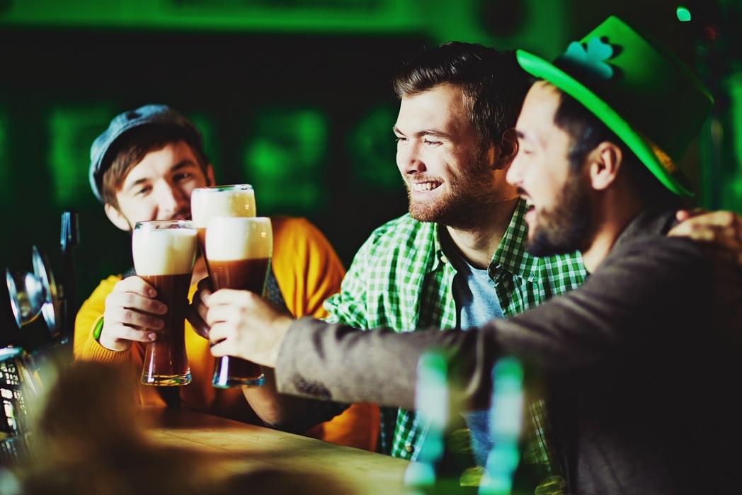 Three men celebrate St. Patrick's Day in a pub
