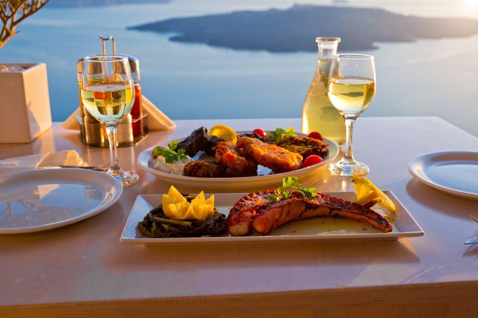 Ποτήρια με λευκό κρασί και μεζέδες με θέα το ηφαίστειο της Σαντορίνης