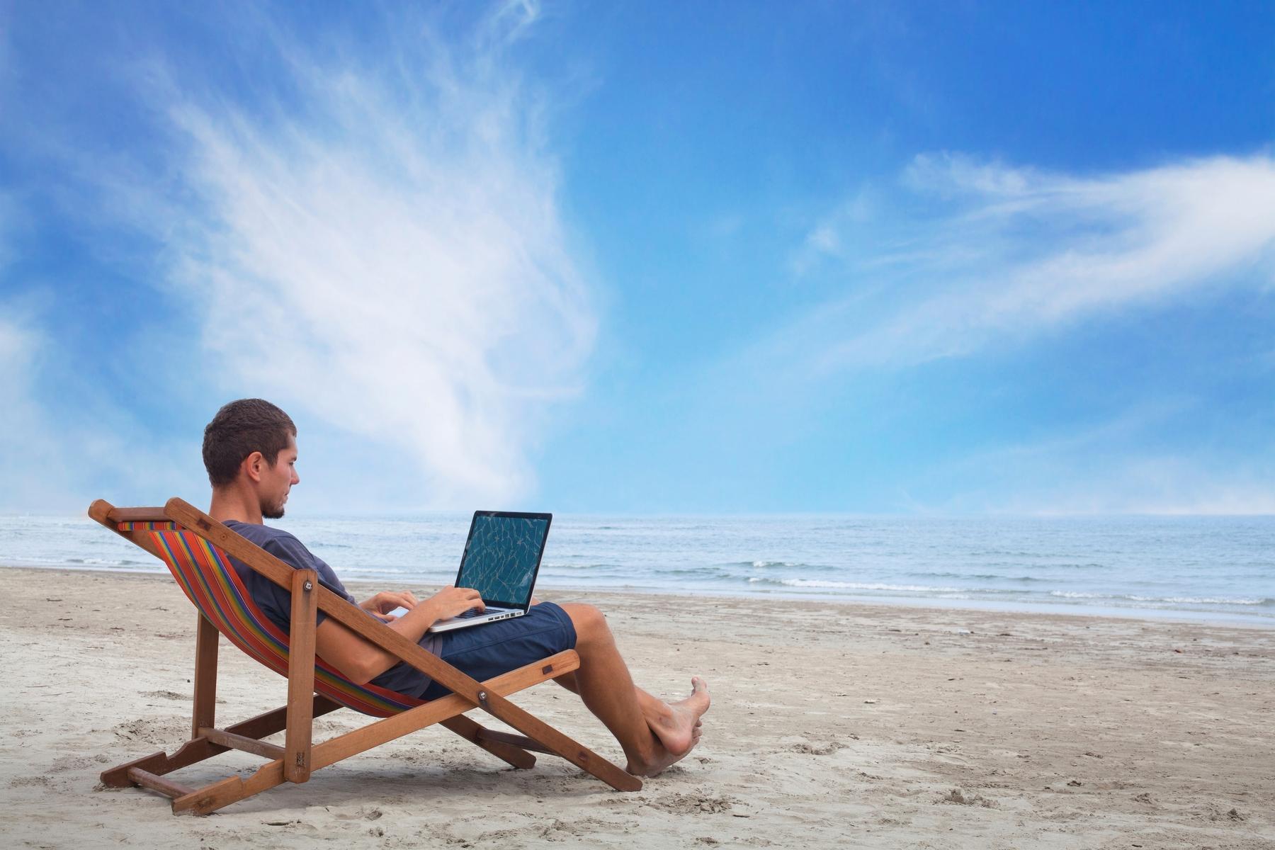 Молодой человек работает за ноутбуком на пляже