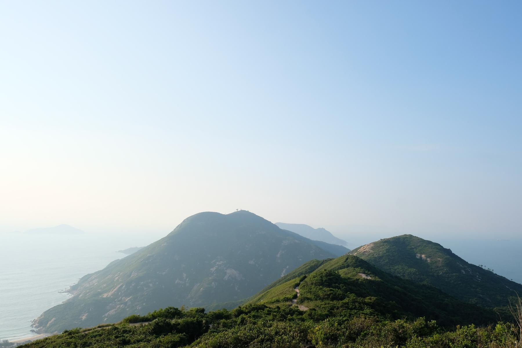 Peak of Dragon's Back hike in Kowloon, HK. Blue and foggy sky.