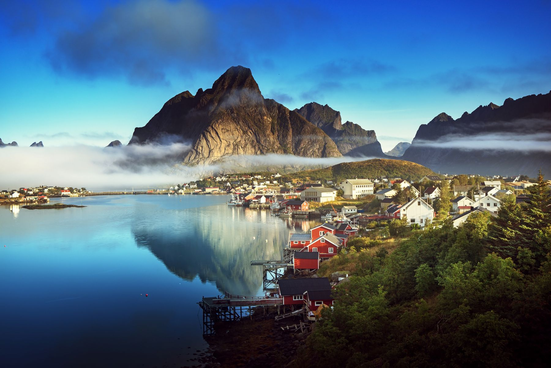 Picture shows the Lofoten Archipelgao, one of our unexpected destinations in Norway. You can see low cloud over blue waters, with mountains in the background and their reflection in the water. Closer to the camera we see red and white houses, and a pier with fishing boats, as well as lots of trees.