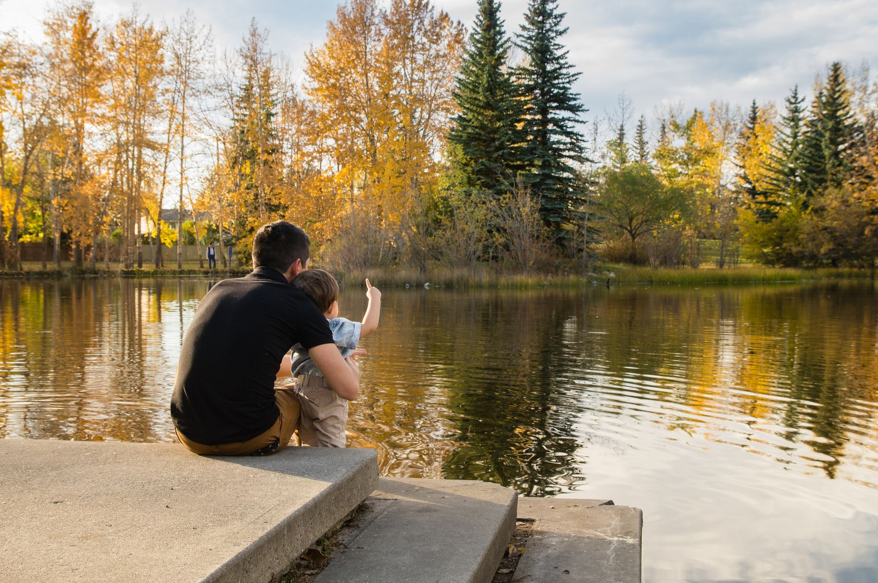 man and boy by a lake pointing at the fall leaves