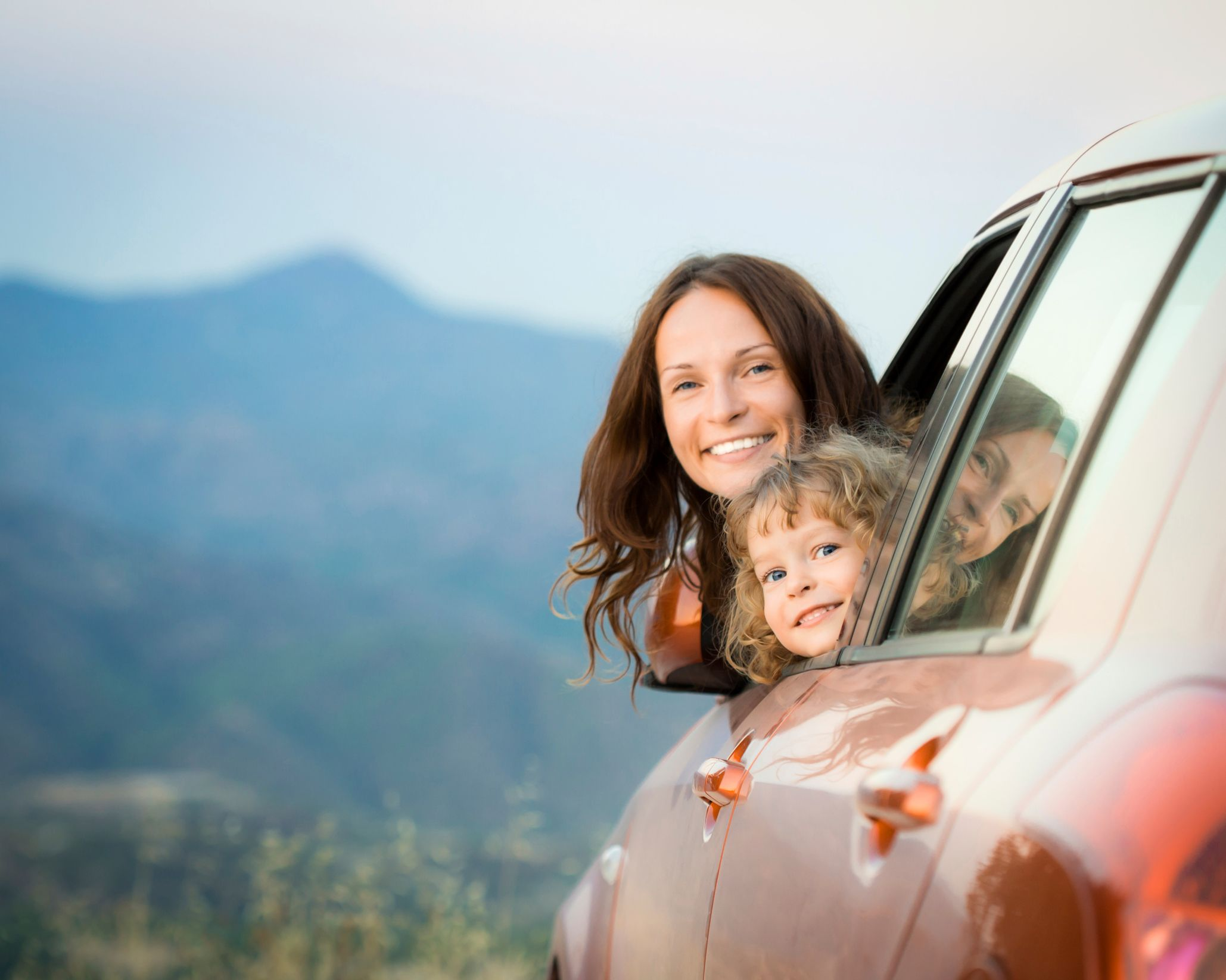 Mother and daughter popping their heads out of a car window