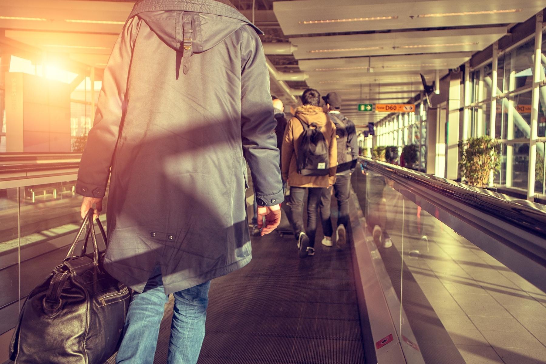 Люди идут по траволатору в аэропорту