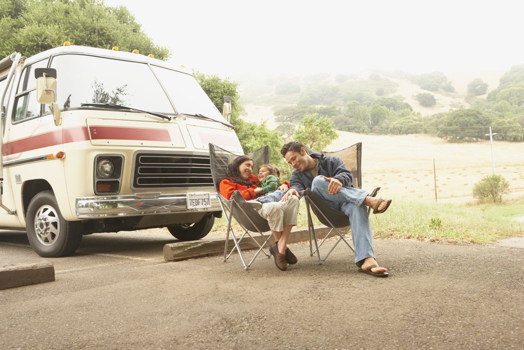 Family resting next to their camper van - road trip with the family