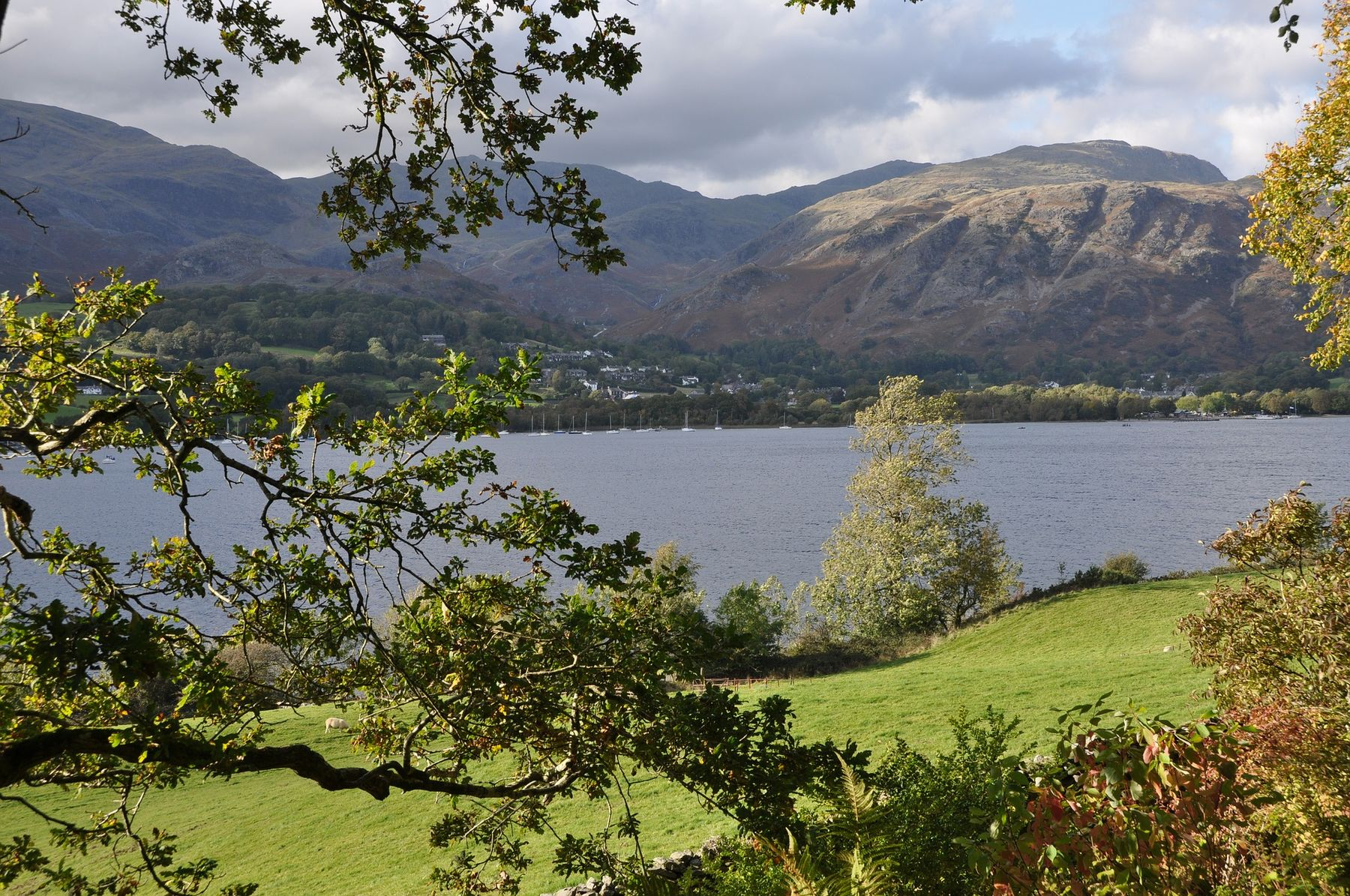 Coniston Water, a lake surrounded by mountains and trees in the Lake District