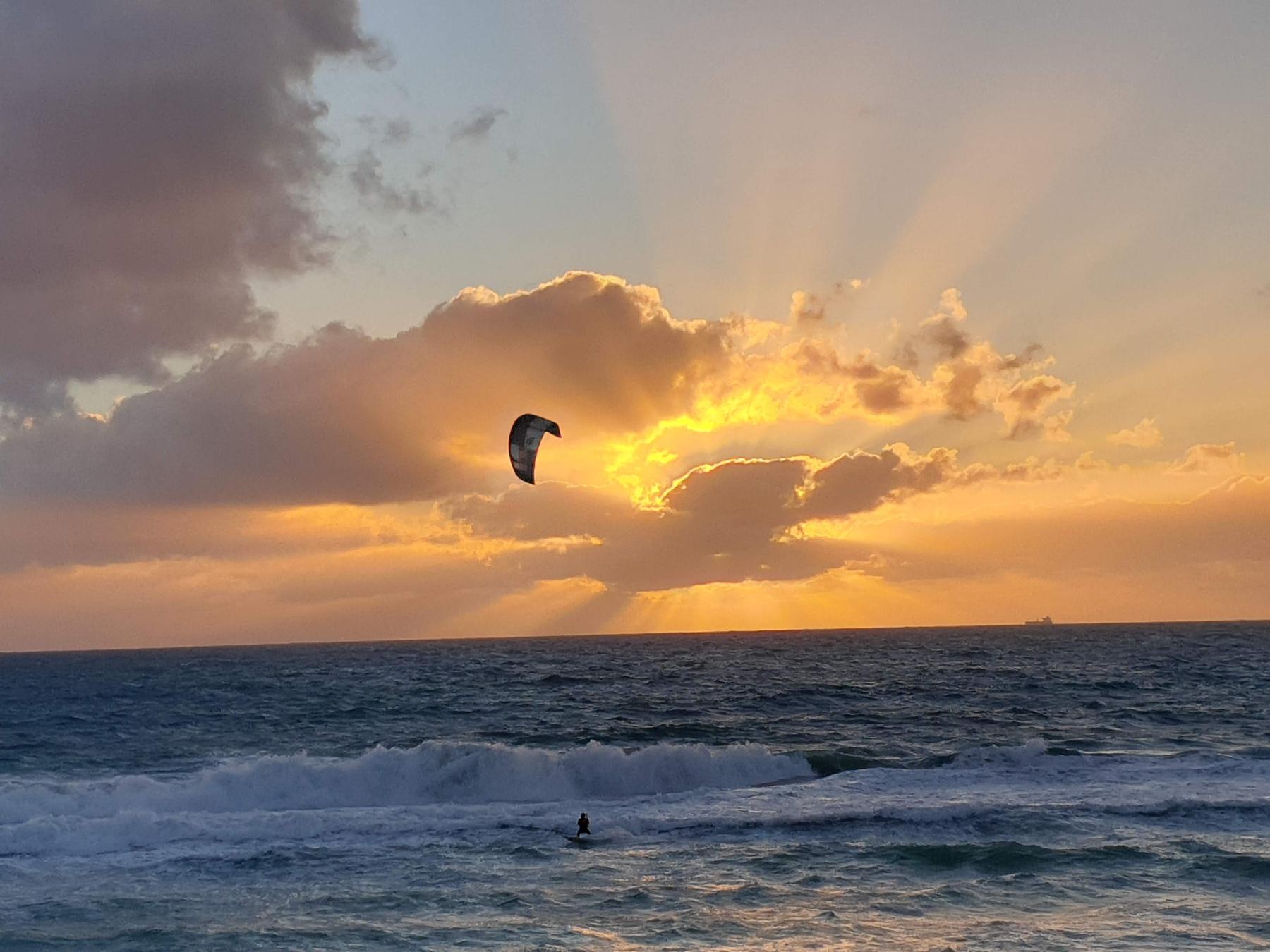 A windsurfer catches a wave off a beach in Western Australia