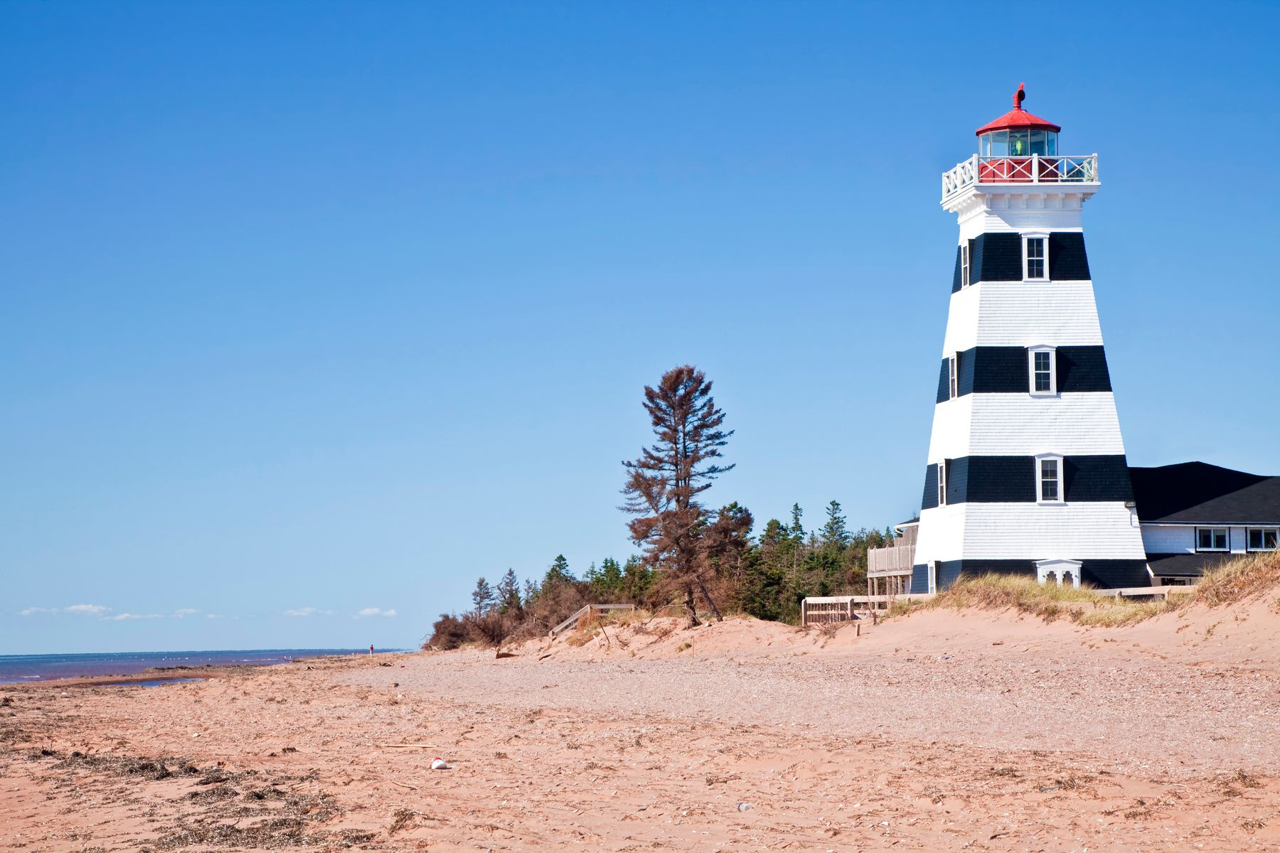 lighthouse by the beach in Prince Edward Island on a sunny summer day