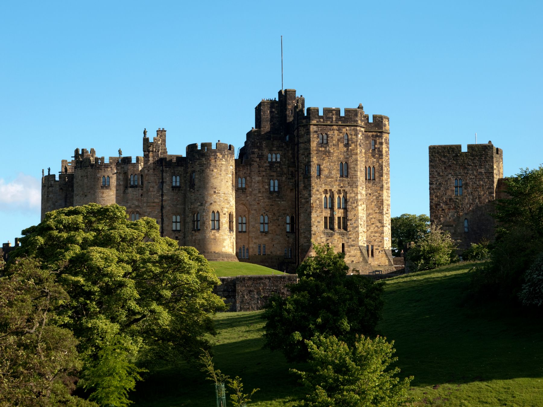 Alnwick castle on top of a green hill with blue sky in the background