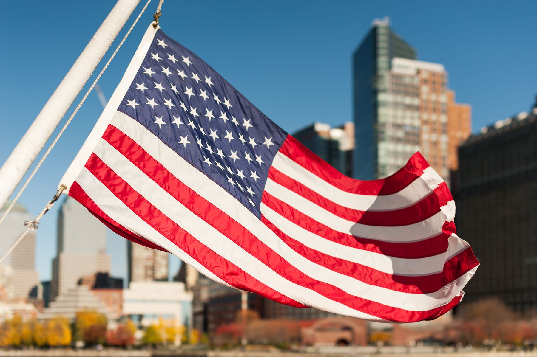 An American flag flies in front of a city skyline. Are you still deciding where to go Memorial Day weekend?