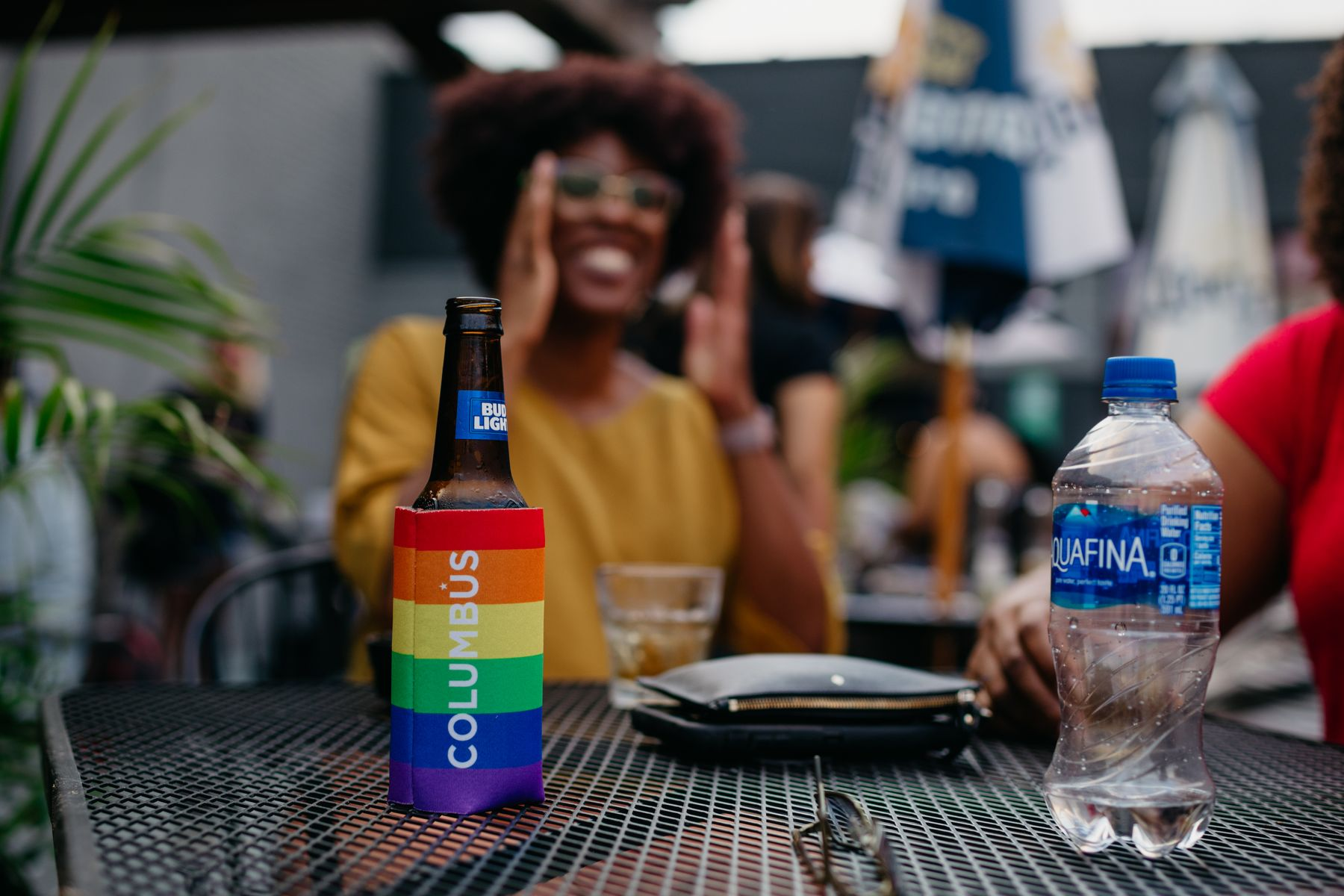 A beer in a rainbow-colored Koozie in focus, with a woman out of focus in the background.