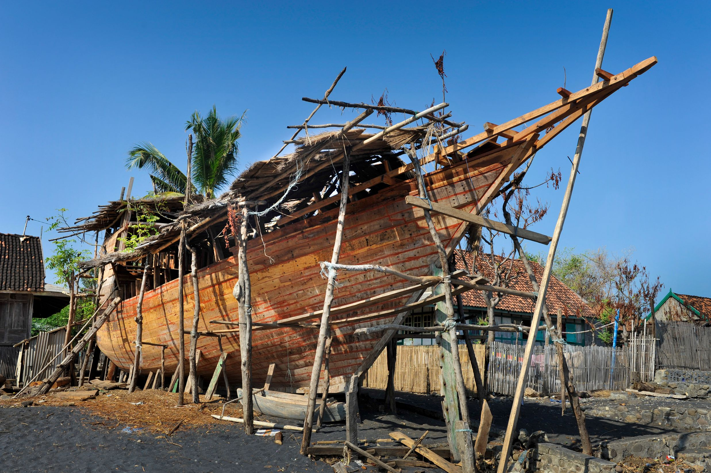 Traditional Indonesian sailing phinisi under construction on beach