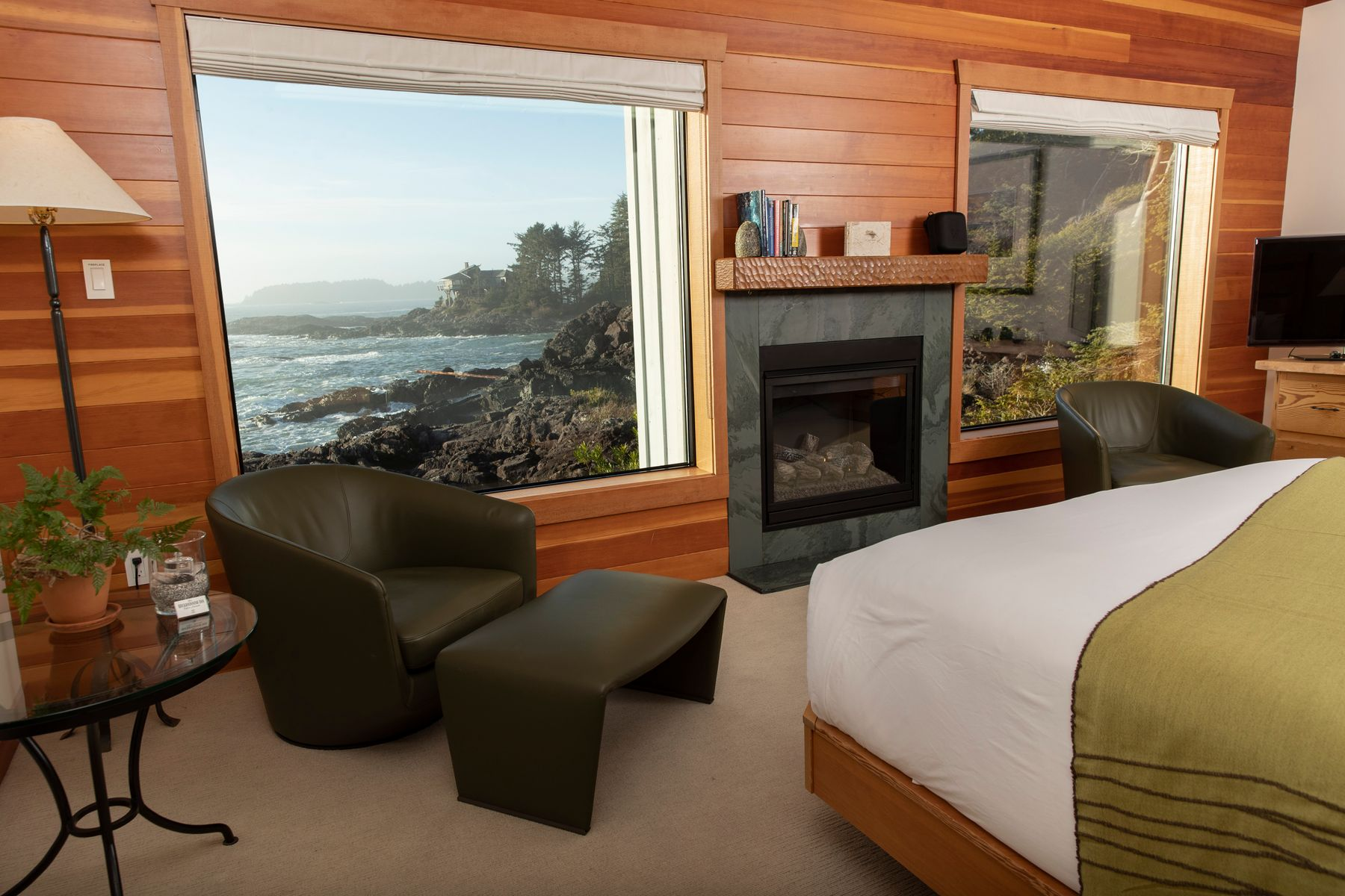 Image of Premier Room in Wickaninnish Inn hotel, a top green hotel in Canada. Hotel bed is made with a green and white blanket on top. Fireplace, table and chair, and view of the Pacific Ccean through the window.