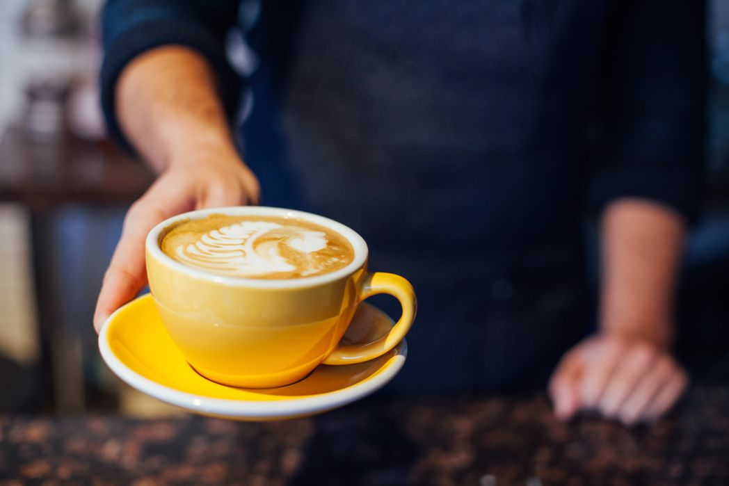 Σερβιτόρος σερβίρει ένα φλιτζάνι ζεστό καφέ.