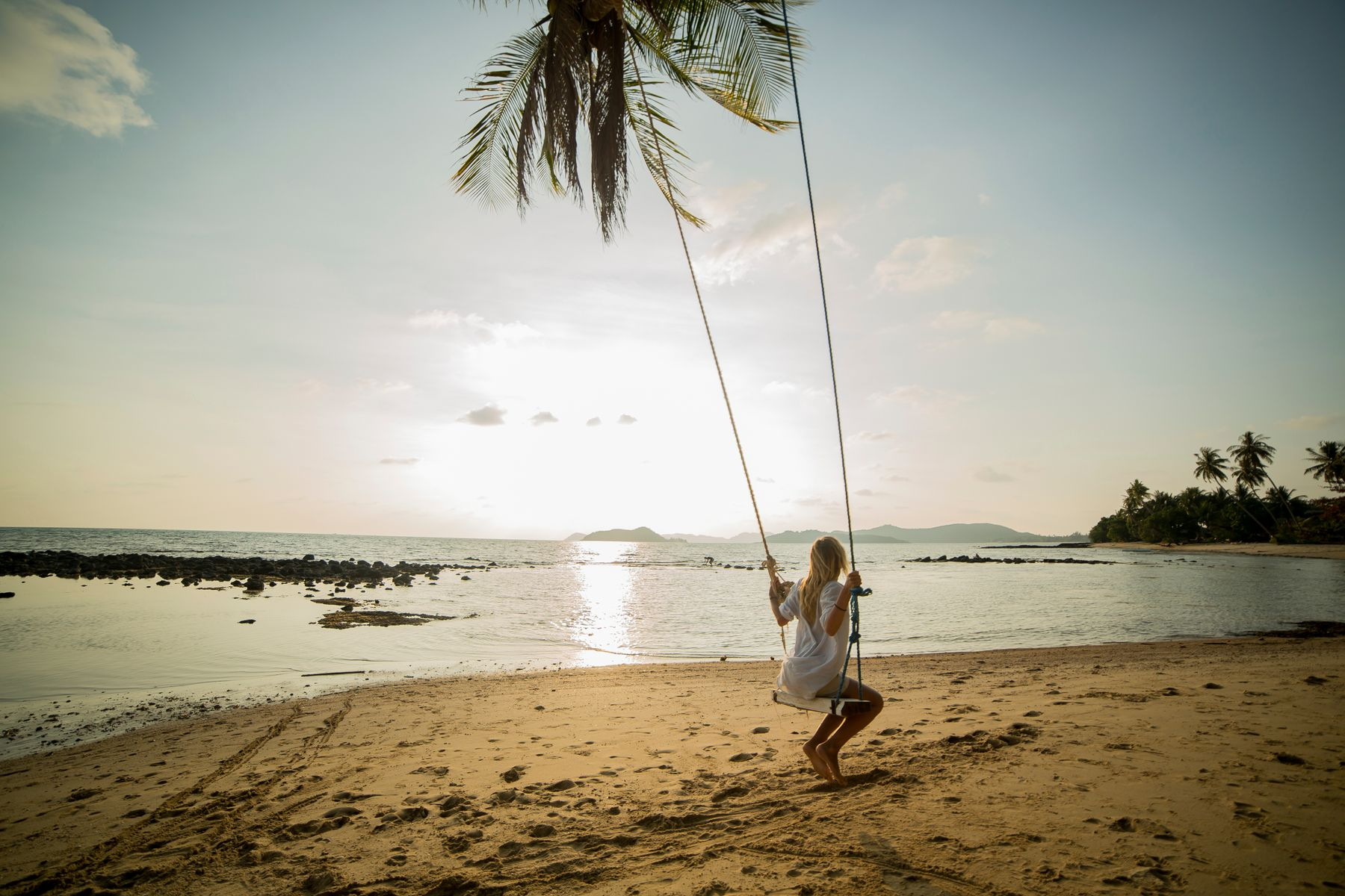 Girl on a swing at sunset on a tropical beach