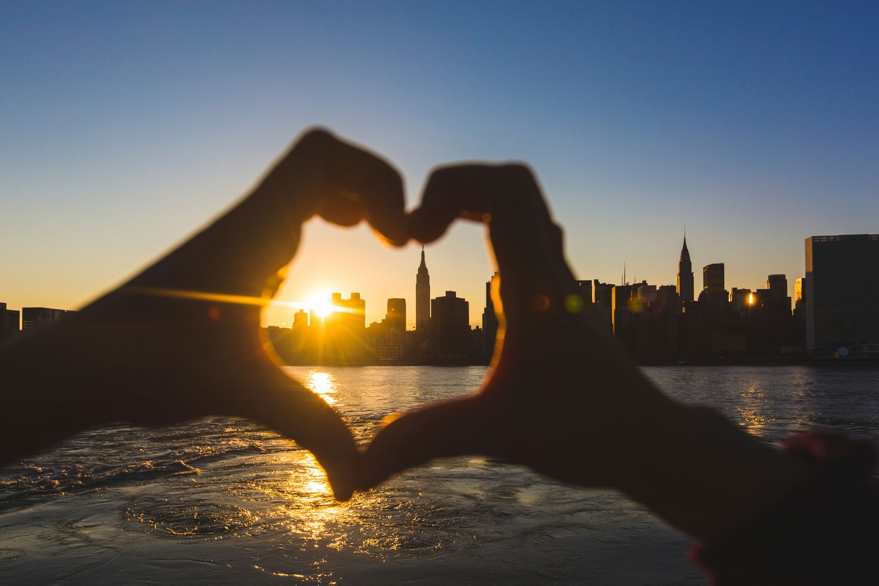 person making a heart shape with their hands with a view of the New York skyline at sunset