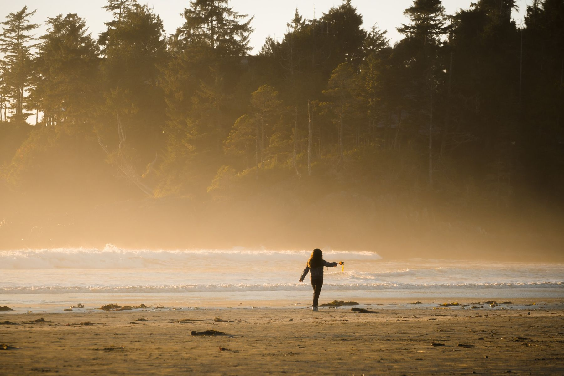 girl walking along the beach in Tofino, BC on a misty day
