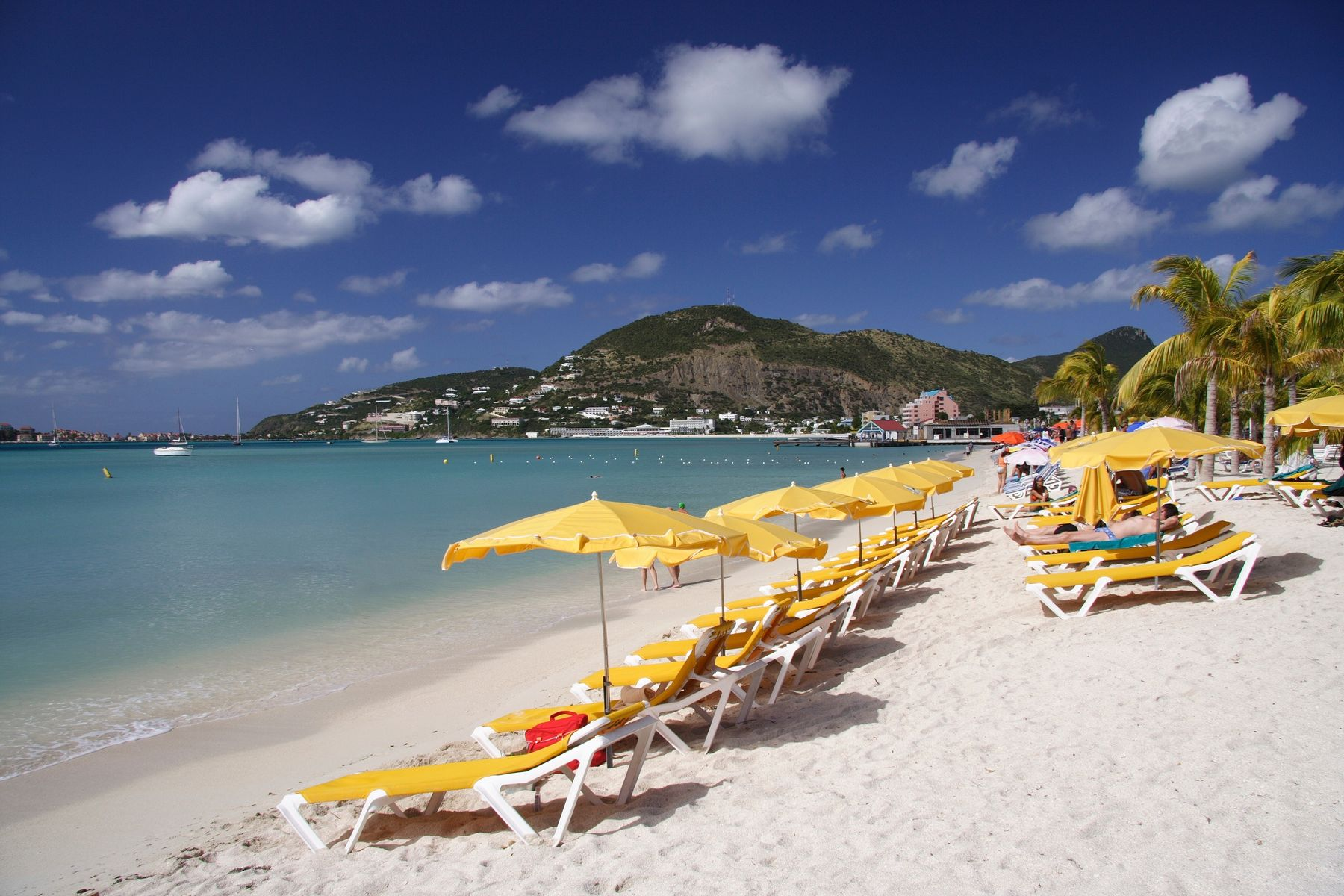 Yellow sunloungers on a white sand beach in Antigua.
