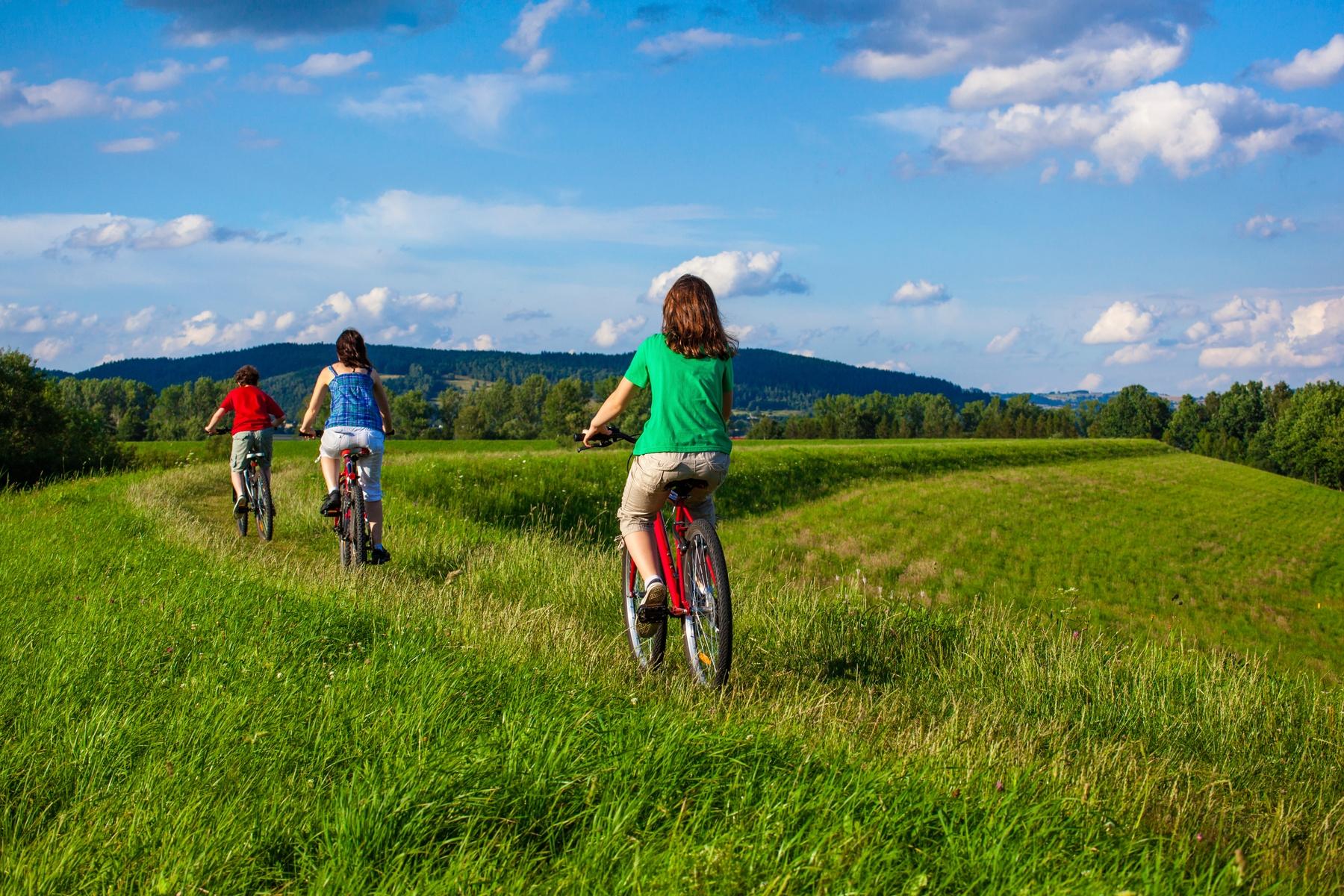 Three children riding their bikes through a grassy field.