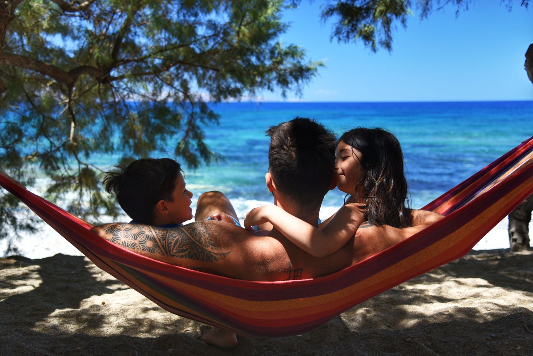 Man lying in a hammock on the beach cuddling with his two children, a boy and a girl,