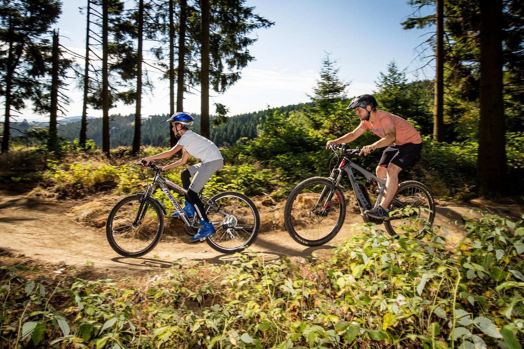 two men biking on a trail